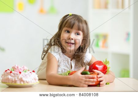 child choosing  healthy vegetables instead of sweet cake