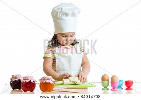 little baker kid girl in chef hat at kitchen