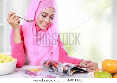 Young Muslim Woman Had A Breakfast While Reading A Magazine