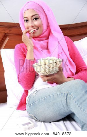 Young Muslim Woman Eating Popcorn