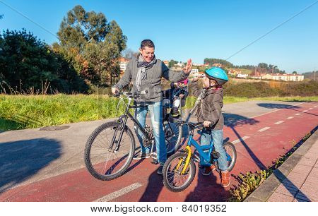 Father and son giving five by success riding bicycle