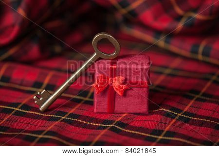 Retro Key And Little Red Gift On A Tablecloth.