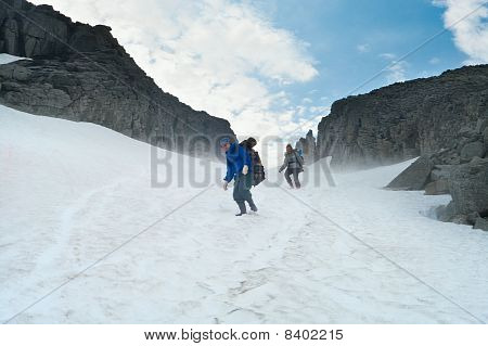 Climbers Walking On Top Of Mountain On Snow.