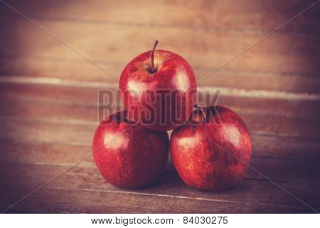 Three Red Apples On Wooden Table. Photo In Retro Color Style.