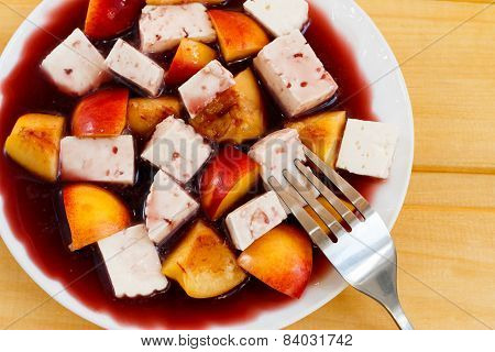fruity salad with cheese in red wine, on wooden desks close-up