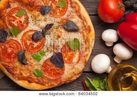 Traditional Pizza Margherita With Tomatoes, Pepper, Olive Oil And Basil On Vintage Rustic Background