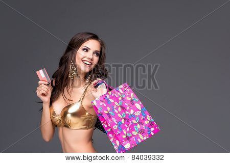 Young Woman With Shopping Bags And Credit Card On A Gray Background