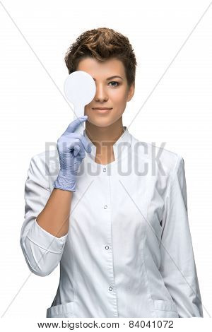 Optometry concept - pretty young woman closes eye
