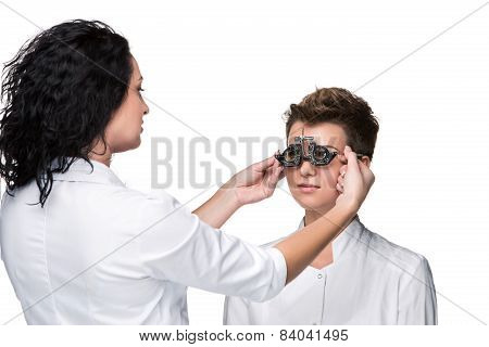 Optometrist holding an eye test glasses and giving to young woman examination