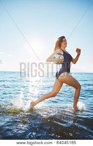 Young woman running in the water with volleyball