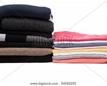 Stacks of winter pullovers and summer t-shirts