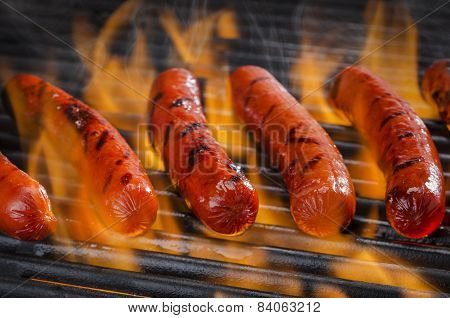 Hotdogs on a Flaming Hot Barbecue Grill