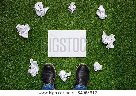 Boots And Sheet Of Paper With Cramled Sheets On The Grass