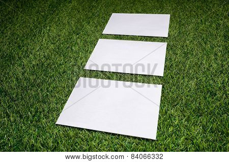 Three White Sheets Of Paper Lying On The Grass