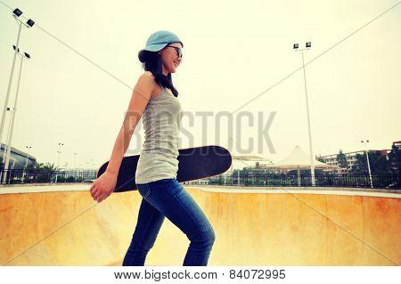 skateboarding woman walking at skatepark