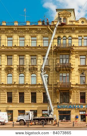 Builders on scaffolding for restoration ancient building in St. Petersburg, Russia