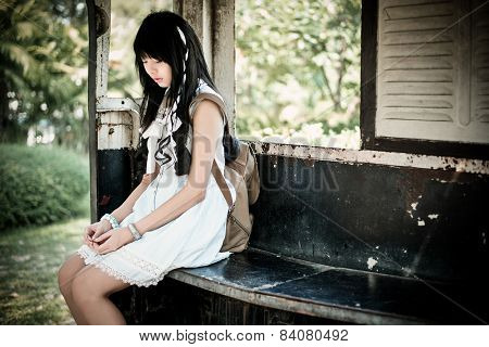 Cute Asian Thai Girl In Vintage Clothes Is Waiting Alone In An Old Bus Stop In Retro Color Tone