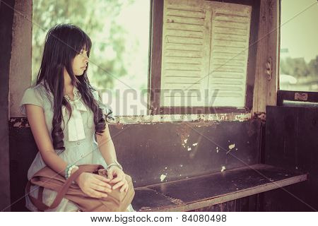 Cute Asian Thai Girl In Vintage Clothes Is Waiting Alone In An Old Bus Stop In Bright Vintage Color
