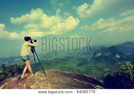 woman hiker photographer taking photo at mountain peak cliff
