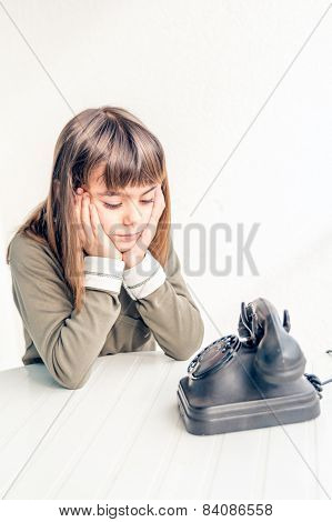Little girl is sitting by the old vintage phone waiting to ring