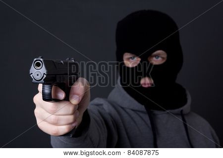 Man In Black Mask Aiming With Gun Over Grey