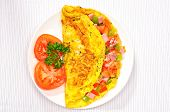 stock photo of pepper  - Delicious omelet with tomato pepper ham basil on a plate - JPG