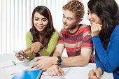 stock photo of handphone  - International group of young students studying together hold handphone  - JPG