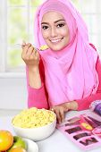 stock photo of muslimah  - portrait of young muslim woman enjoy eating a cereal while reading a magazine - JPG