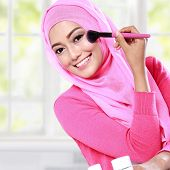 stock photo of hijabs  - portrait of cheerful young woman wearing hijab applying blush on - JPG