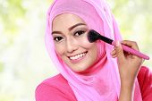 stock photo of muslimah  - close up portrait of cheerful young muslim woman applying blush on - JPG