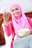 pic of muslimah  - morning activity of young muslim woman watching television while eating popcorn - JPG