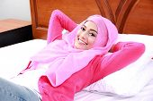 stock photo of muslimah  - portrait of cheerful young woman wearing pink hijab lying on bed - JPG
