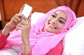 picture of muslimah  - portrait of cheerful young muslim woman lying on bed while playing mobilephone - JPG