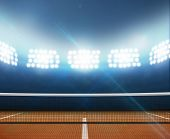 foto of arena  - A tennis court in an arena with a marked orange clay surface at night under illuminated floodlights - JPG