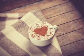 image of orientation  - Cup with coffee and shape of the cacao heart on it and scarf - JPG