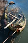 picture of neglect  - Half sunk neglected oxidized iron rowboat full of lodgers - JPG