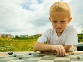 image of daycare  - Draughts board game. Little boy clever child kid playing checkers thinking outdoor in the park. Childhood and development