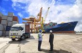 picture of shipyard  - foreman control Industrial Container Cargo freight ship from his manager with working crane bridge in shipyard with truck - JPG