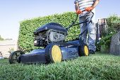 picture of angle  - A low angle view of a man preparing for lawn mowing - JPG