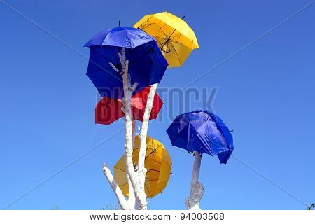 Abstract colorful umbrellas over blue sky
