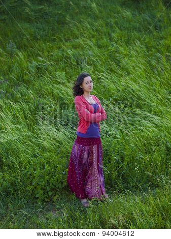 Girl In Eastern Dress, Stands In A Field In The Wind.