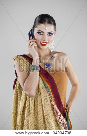 Young traditional Asian Indian woman calling by phone