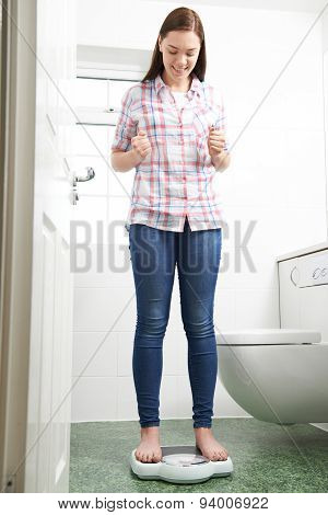 Happy Teenage Girl Standing On Bathroom Scales