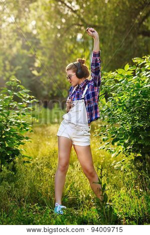 Hipster Girl With Headphones And Cell Phone In Park Dancing.
