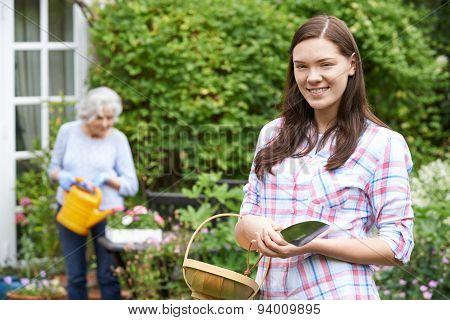 Teenage Granddaughter Helping Grandmother In Garden