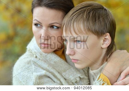Sad mother with son in autumn park