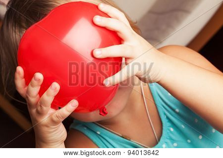 Baby Girl Holds Small Red Heart Shaped Balloon
