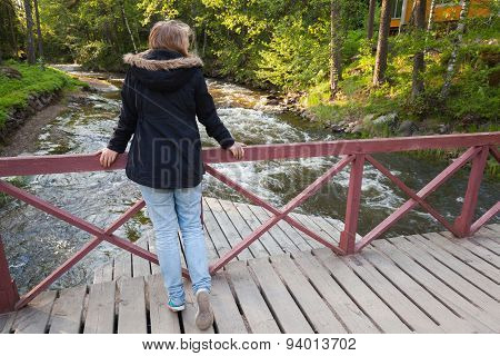 Caucasian Teenage Girl Stands On Wooden Bridge
