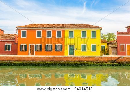 Colorful apartment building with nice waterfront view in Burano, Venice, Italy.