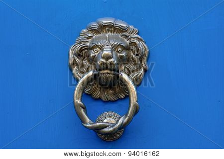 Lion Head Door Knocker On A Blue Door